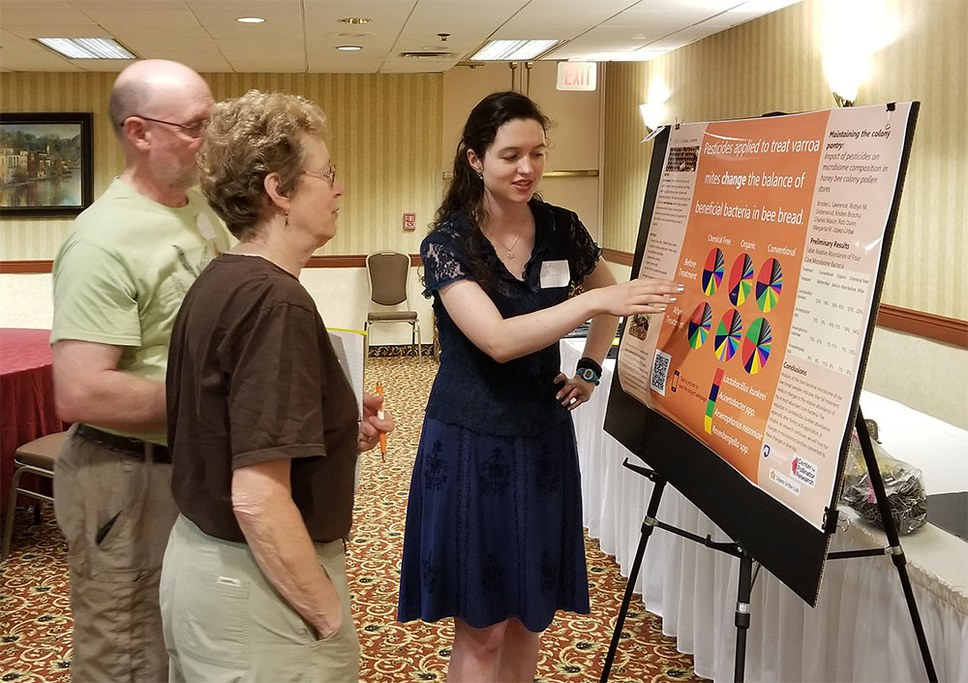 """Brooke Lawrence presents her research poster titled """"Maintaining The Colony Pantry: Impact Of Pesticides On Microbiome-Mediated Pollen Preservation In Honey Bee Colonies"""" to participants at the 2nd Pollinator In-service Meeting. Photo by Shelby Kilpatrick."""
