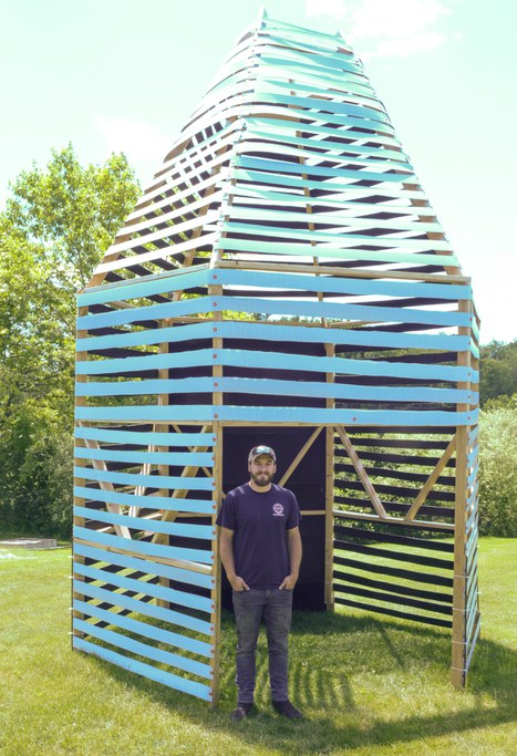 "Rising senior, Matthew Poorman stands next to the 18-foot prototype ""Bee Hut."" The pavilion design is modelled after old skeps, which were baskets used to house honey bees before Langstroth hives."