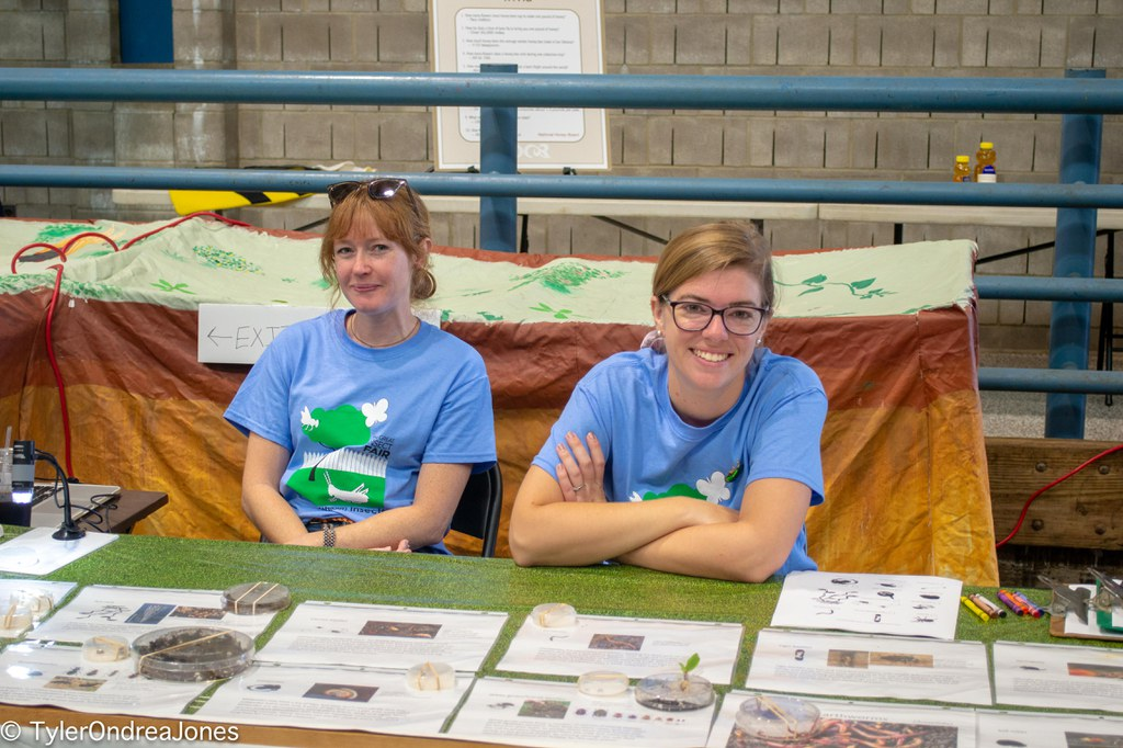 """PSU Graduate students Elizabeth Rowen (right) and Liz Davidson-Lowe (left) sitting outside of the """"Haunted Soils"""" Exhibit at the 2019 Great Insect Fair."""