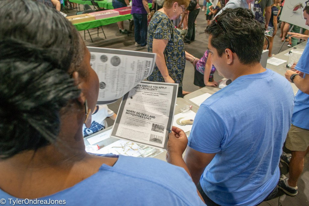 """PSU Graduate students Fhallon Ware-Gilmore (left) and Mario Novelo Canto (right) heading the """"Mosquito Biology"""" booth at the 2019 PSu Great Insect Fair. Ware-Gilmore can be seen flipping through a fact sheet on vector control that includes updated information on mosquito-vectored diseases and how to prevent them."""