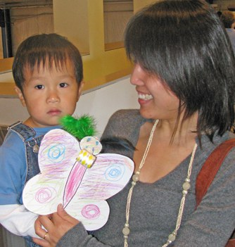 Child & mother holding moth mask